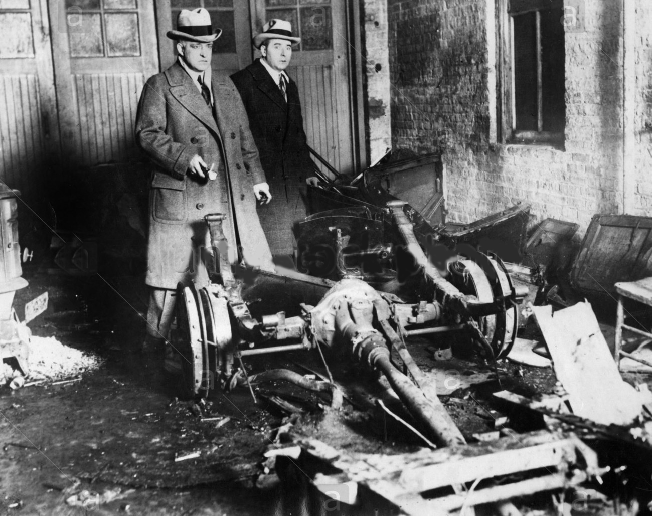 REMNANTS OF AUTO THOUGHT TO BE GARAGE MASSACRE DEATH CAR. Chief Of  Detectives John Egan (left) And Capt. Daniel Gilbert Looking Over Burned  And Battered ...